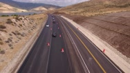 Aerial static shot cars drive through a construction zone Stock Footage