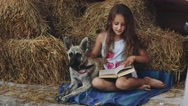 Young Curly Girl Reads a Book With His Dog Stock Footage
