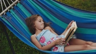 Young Curly Girl Reads a Book Lying in a Hammock Stock Footage