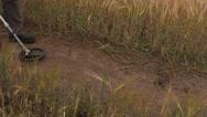 Man using Metal Detector on a Field Road. Pan Stock Footage