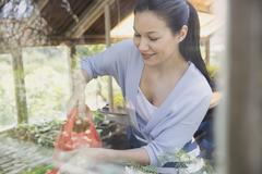 Smiling woman gardening with watering can in greenhouse Stock Photos