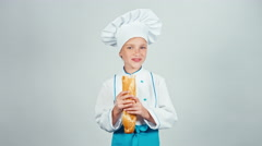 Happy baker girl 7-8 years child eating baguette bread and smiling at camera Stock Footage