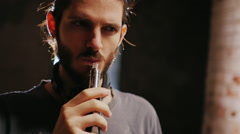 Young hipster man smokes an electronic cigarette, effectively produces steam in Stock Footage