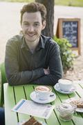 Portrait smiling man enjoying cappuccino at outdoor cafe table Stock Photos
