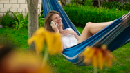 Beautiful girl talking on the phone while lying in a hammock. Stock Footage
