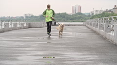 Cute Retriever and His Owner Running Along Pier Stock Footage