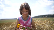 Girl with flower sitting on the hay in a field Stock Footage