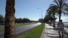 Tourists and citizens on the seafront street of Palma de Mallorca Stock Footage