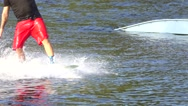 Wakeboarder in red shorts riding a wakeboard, slow motion Stock Footage