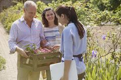 Plant nursery worker helping couple shopping for flowers in sunny garden Stock Photos