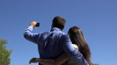 Couple of lovers standing with back taking a picture, a selfie, blue serene sky Stock Footage