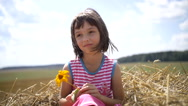 Girl with flower sitting on the hay looking at the camera and smiling Stock Footage