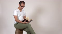 Young man in black rim glasses reads a book sitting on a big stack of books Stock Footage
