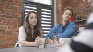 Three cheerful young people discussing project. Stock Footage