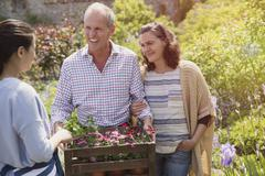 Plant nursery worker helping smiling couple with flowers in garden Stock Photos