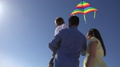 Young family with a colored kite, parents and child enjoying carefree flight  Stock Footage