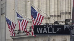 Wall Street road sign with American flag & NYSE behind, New York. Stock Footage