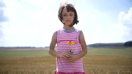 Girl with a flower standing in a field looking at the camera Stock Footage