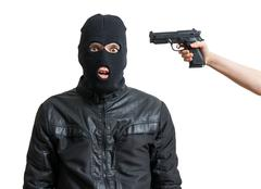 Arrested burglar or robber isolated on white background. Hand is aiming with  Stock Photos