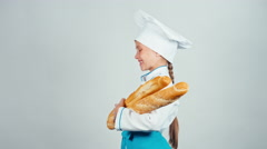 Baker girl 7-8 years child holds bread baguettes and smiling at camera on white Stock Footage
