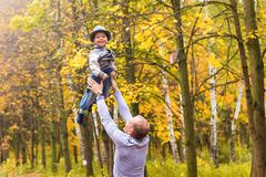 Father throws his happy laughing son in the air in the autumn park Stock Photos