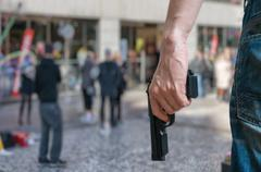 Armed man (attacker) holds pistol in public place. Many people on street. Gun Stock Photos