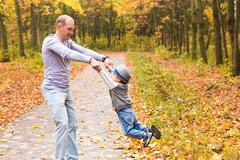 Father throws his happy laughing son in the autumn park Stock Photos