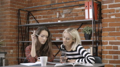 Two beautiful young girls studying at modern loft apartment. Stock Footage