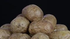 Ukrainian national dish is baked potatoes. Potato on a black background rotates Stock Footage