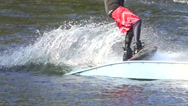 Man rides a wakeboard in red shorts on to the springboard, slow motion Stock Footage
