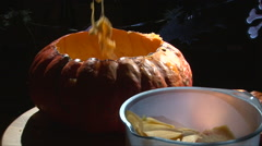 Sequence scooping flesh and seeds from Halloween Pumpkin Stock Footage
