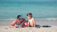 Father and son laying down on seashore, play with snorkeling equipment Stock Footage