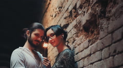 Young gothic hipster couple admires the sparkler. Standing against a background Stock Footage