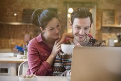Smiling couple drinking coffee using laptop at cafe Stock Photos