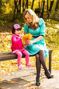 Young mother and her toddler girl have fun in autumn Stock Photos