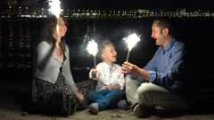 Happy family with sparkling fireworks, special night on seaside, celebration Stock Footage