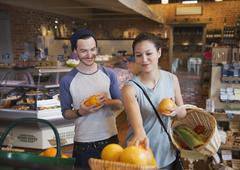 Couple shopping for oranges in market Stock Photos