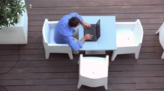 Young man working on a laptop at a summer terrace, up view Stock Footage