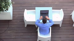 Man working at computer on summer terrace, aerial view Stock Footage