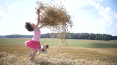 Children play with hay, throw the hay up on the mountain Stock Footage
