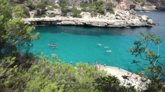 Green pines trees, turquoise water, people on seashore, idyllic summer holiday Stock Footage