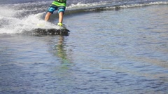 Wakeboarder rides a wakeboard in colorful shorts, slow motion Stock Footage