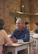Smiling couple talking in cafe Stock Photos