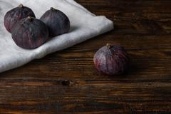 Ripe seasonal figs on the cloth and wooden surface Stock Photos