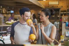 Couple smelling grapefruits in market Stock Photos