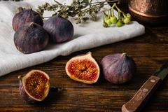 Ripe figs on cloth with sliced one and some objects Stock Photos