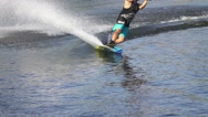 Wakeboarder man rides a wakeboard in turquoise shorts, slow motion Stock Footage