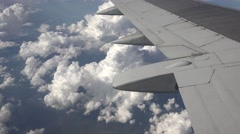 Airplane wing flying over white fluffy clouds Stock Footage