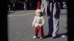 1954: a man in a suit adjusting a small boy's outfit in the street PENNINGTON, Stock Footage