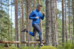 Runner jumping over fallen log on trail in woods Stock Photos